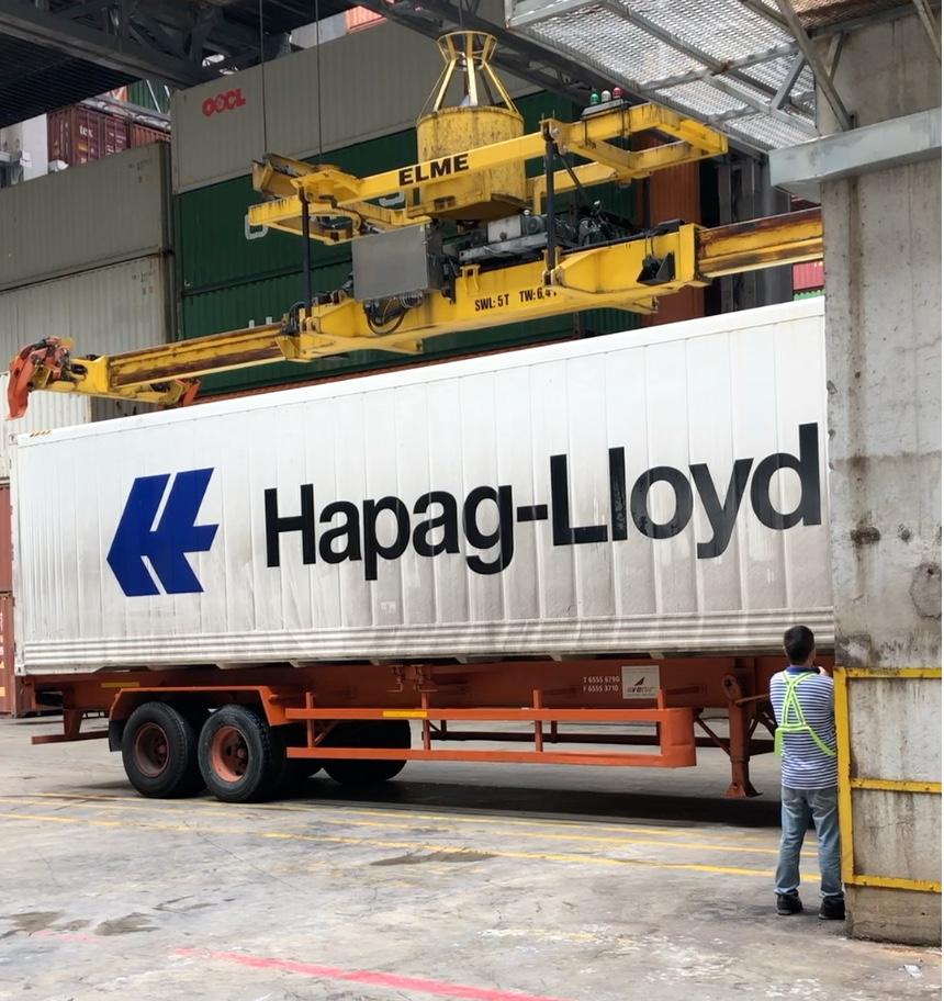 An overhead crane handling a road truck