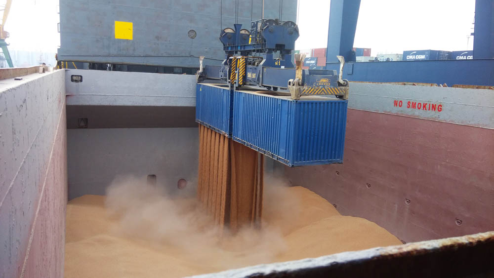 A dedicated containerised bulk handling system using a container rotator