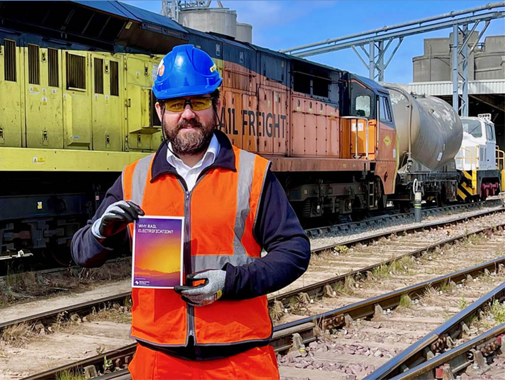 Furrer+Frey's Noel Dolphin holding the Railway Industry Association's Why Rail Electrification report at the Dunbar test site
